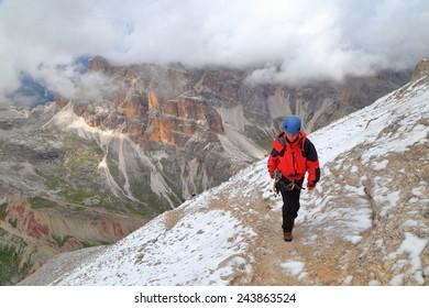 "Snow covered trail and woman climber ascending via ferrata ""Lipella"", Tofana massif, Dolomite Alps, Italy"