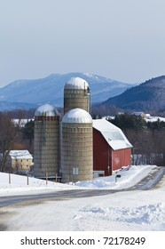 Snow covered Vermont farm nestled in the mountains on an overcast morning