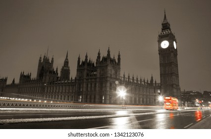 Snow covered Westminster Palace at dawn over dark grey sky. Nobody present on wet the street.