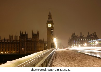 Snow covered Westminster Palace at dawn over dark grey sky. Fast moving bus left lights trail and nobody present on the wet street.