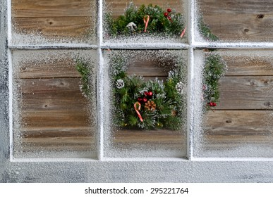 Snow covered window with decorative Christmas wreath on rustic wooden boards in background. Focus on window glass and sills.