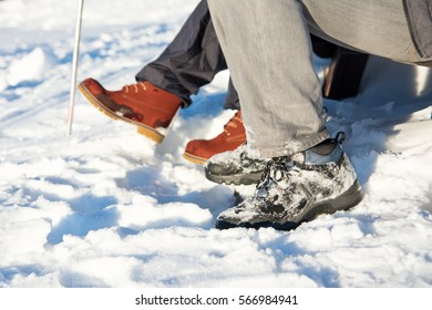 Snow covered winter boots and hiking stick