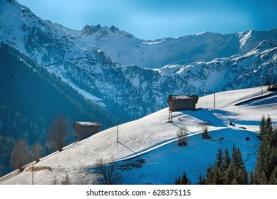 snow covered winter scenery in the mountains with wooden hay huts at Gailvalley, Carinthia, Austria