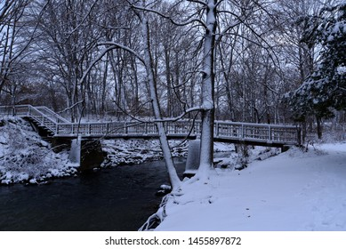 A snow covered wooden bridge over the open water of the Pike River in a Wisconsin park early in the winter season.