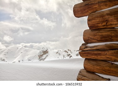 Snow covered wooden cabin facing the snowy peaks of mountains in the cold winter.