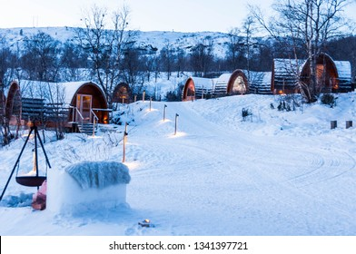 Snow covered wooden cabins (Gabba) designed after the indigenous Sami lavvu (tents). Kirkenes, Norway