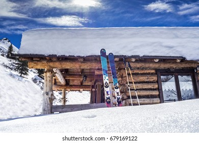 Snow covered wooden hut with skis