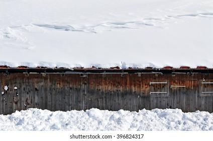Snow covers the roof of a wooden structure during winter.
