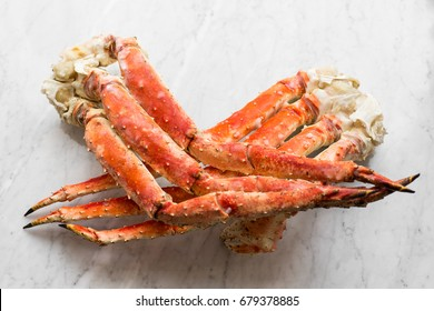 Snow Crab Legs on a light marble. Selective focus