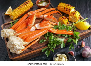 snow Crab legs served with melted butter in clay bowls, garlic cloves, lemon slices, grilled corn in cobs and fresh parsley on wooden cutting boards, horizontal view from above, close-up