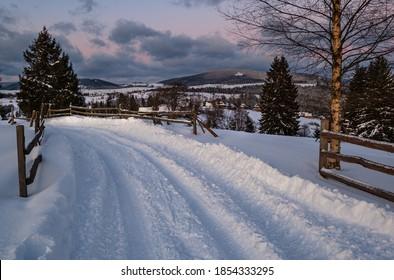 Snow drifts on road through twilight small and quiet winter alpine village, Voronenko, Carpathian, Ukraine. Night countryside hills, groves and farmlands in remote alpine village.