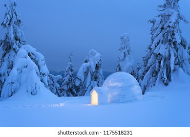 Snow eskimo igloo for spending the night in a mountain forest. Extreme adventures in nature in the winter. Evening Landscape with shelter for extreme tourists