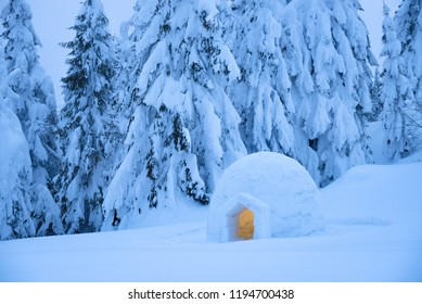 Snow eskimo igloo for spending the night in a mountain forest. Extreme adventures in nature in the winter. Evening Landscape with shelter for tourists