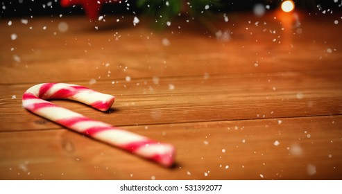 Snow falling against candy cane on wooden table