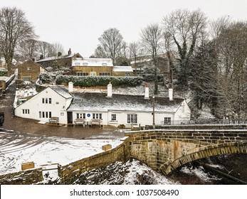 Snow falling the Old Bridge public house, Calderdale, West Yorkshire, UK