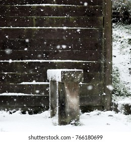 Snow falling on a bench with wooden backdrop.