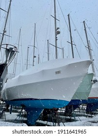 Snow falling on covered boats as winter sets in on the boatyard in East Boston.