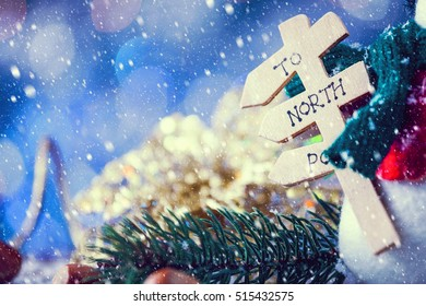 Snow Falling On Snowman Closeup On Snowy Christmas Wooden Background Holding Sign To North Pole. Selective Focus With Copy Space. Vintage Filter Applied.