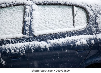 snow fals on door and windshields of blue car