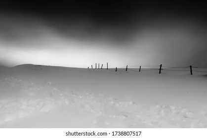 A snow field and a barbed wire fence