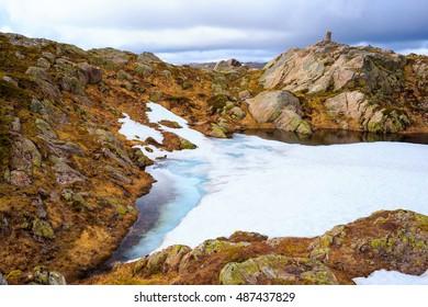 Snow field near trail in Norway mountain range, summer