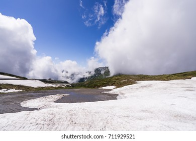 Snow field on the mountain in national park with blue sky and many clouds.