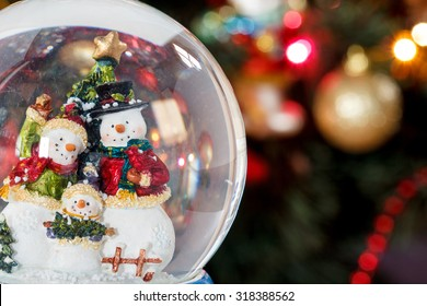 Snow globe with happy snowman family on christmas tree blured background