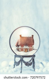 Snow globe on an antique silver stand in snowfall for Christmas holidays with festive golden tree