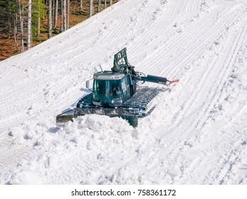Snow groomer prepare ski piste among of the forest on ski resort in Carpathians