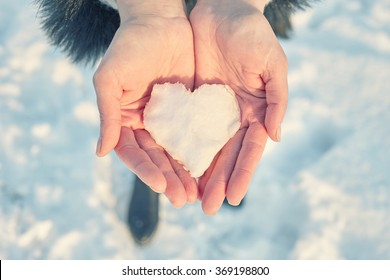 snow heart in female hands, toned image