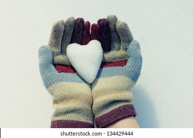 Snow heart in hands. Closeup shot
