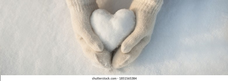 Snow heart in hands. Human hands in warm beige gloves with snowy heart against snow background. I love winter or St.Valentine's Day romantic creative concept. Panorama banner with free space for text