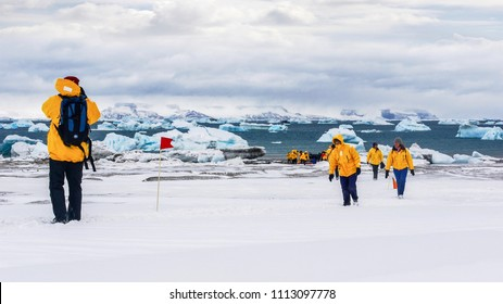 Snow Hill Island, Antarctica - December 5, 2010: Illustrative Editorial. Showing tourism in Antarctica, as tourists wearing matching parkas walk across snow, with sea and icebergs in the background.