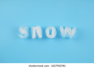 Snow ice alphabet made of ice cubes on blue background.