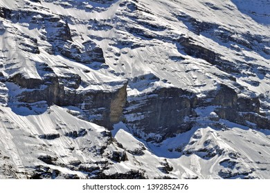 snow and ice covered cliff of swiss alps mountain