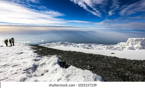 Snow, ice and glaciers on top of mount Kilimanjaro at sunrise with clouds in the sky background and people climbing to summit, Africa