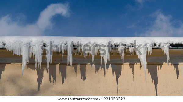Snow and ice icicles on the roof of the building. Frozen water in white icicles. Contrasting shadows. Panoramic view. Blue sky with clouds.