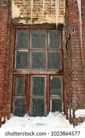 Snow and icicles on the facade of the house. A window in an old, ruined house.