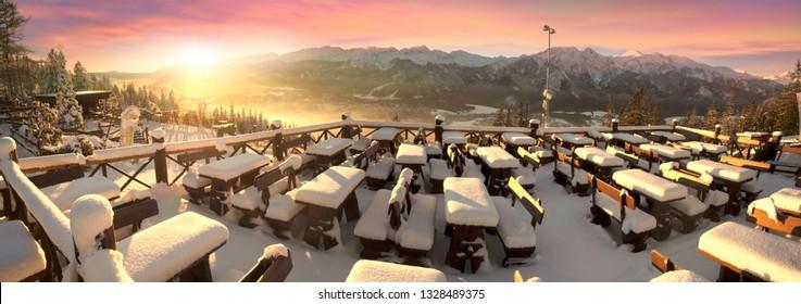 The snow lies on the tables of the café of the ski and tourist resort of the Polish city of Zakopane on the Gubałówka mountain, opposite the peak of the Tatras