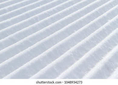 Snow lines made by a snow machine or snowcat on a ski slope in Bavaria, Germany.