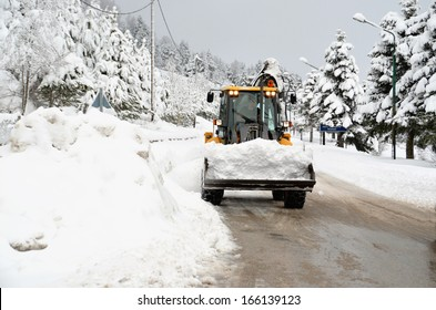 snow loader  cleaning road from ice - winter transportation background