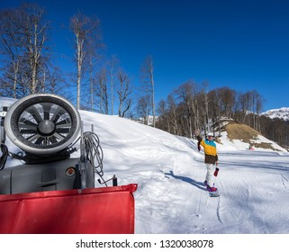 Snow machine gun and snowboarder woman standing at slope of track on background mountain scenery of the Caucasus mountains in Krasnaya Polyana