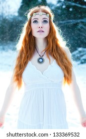Snow Maiden. Whimsical image of beautiful red head woman standing in snow looking angelic