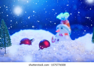 Snow Man with Christmas balls on snow over fir-tree, night sky and moon. Shallow depth of field. Christmas background. Fairy tale. Macro. Artificial magic dreamy world.