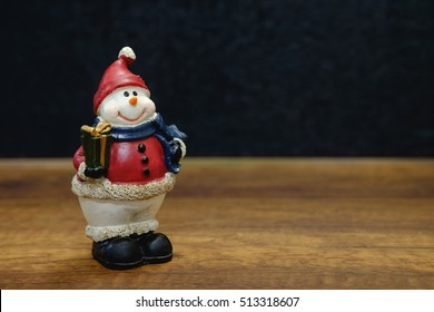 Snow man statue on wooden table with black background.