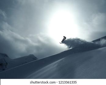 Snow mobile hitting jump