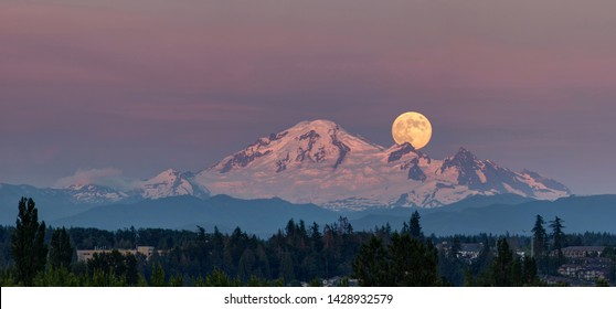 snow mountain with full moonrise at sunset