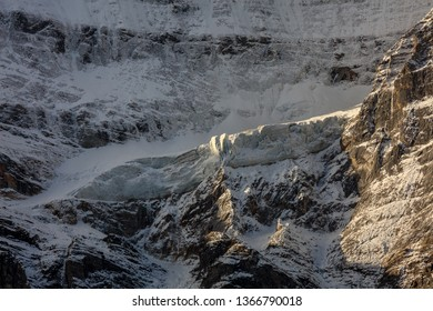 Snow Mountain, Massive Glacier, Wall of Ice, Mountain Cliff Face covered in ice, blue glacial ice, pure white snow covered landscape, high altitude landscape, avalanche risk, melting glaciers