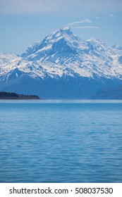 Snow mountain peak under clear blue sky with turquoise colored water of lake Pukaki, New Zealand
