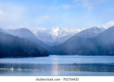 Snow Mountains and Capilano Lake at fog in Vancouver British Columbia Pacific Northwest.